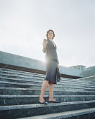 Businesswoman descending steps looking at mobile phone, low angle view