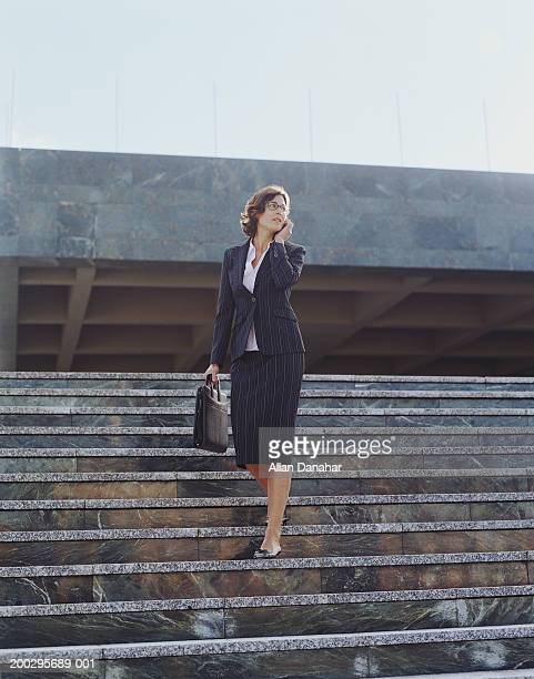 Businesswoman descending steps, using mobile phone, low angle view