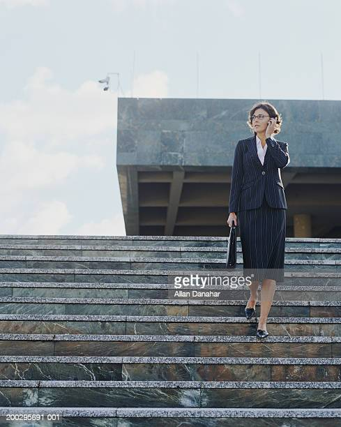 Businesswoman descending steps using mobile phone, low angle view