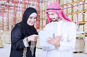 Muslim businesswoman discussing with her partner by using digital tablet in warehouse