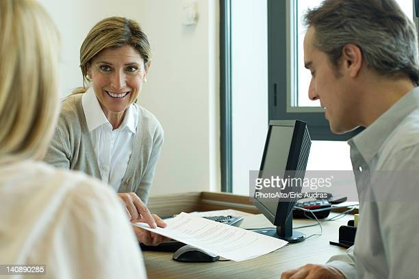 Businesswoman discussing contract with clients
