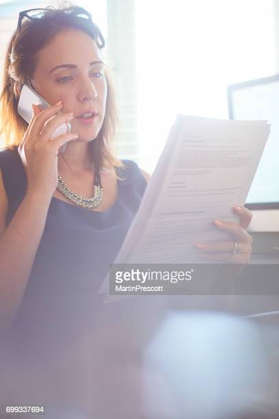 Businesswoman discussing paperwork on the phone