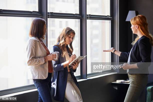 Businesswoman discussing with colleagues by window