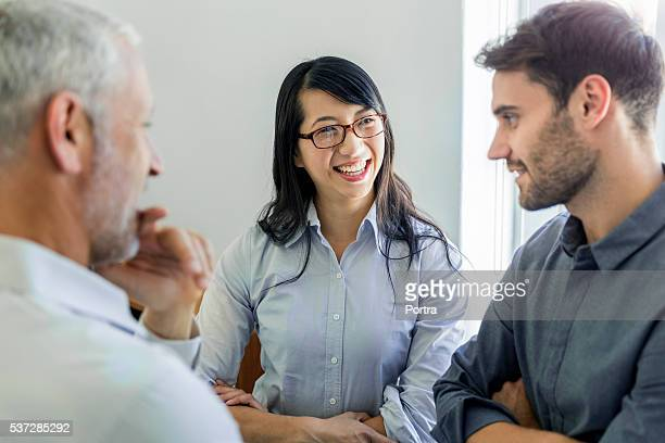 Businesswoman discussing with coworkers in office