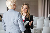Businesswoman discussing with female colleague in seminar hall