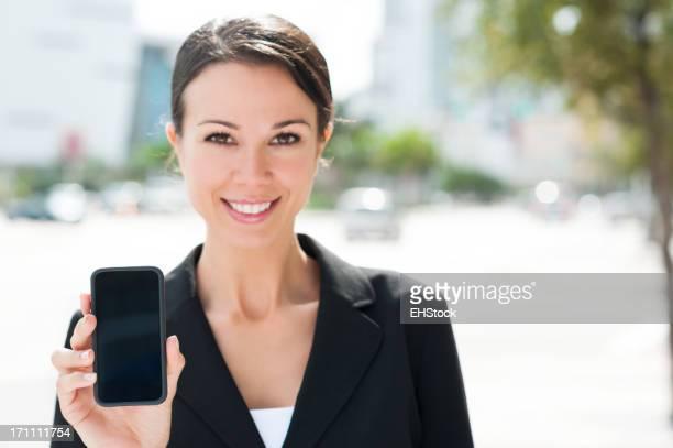 Femme d'affaires affichage de Smartphone téléphone portable dans la rue