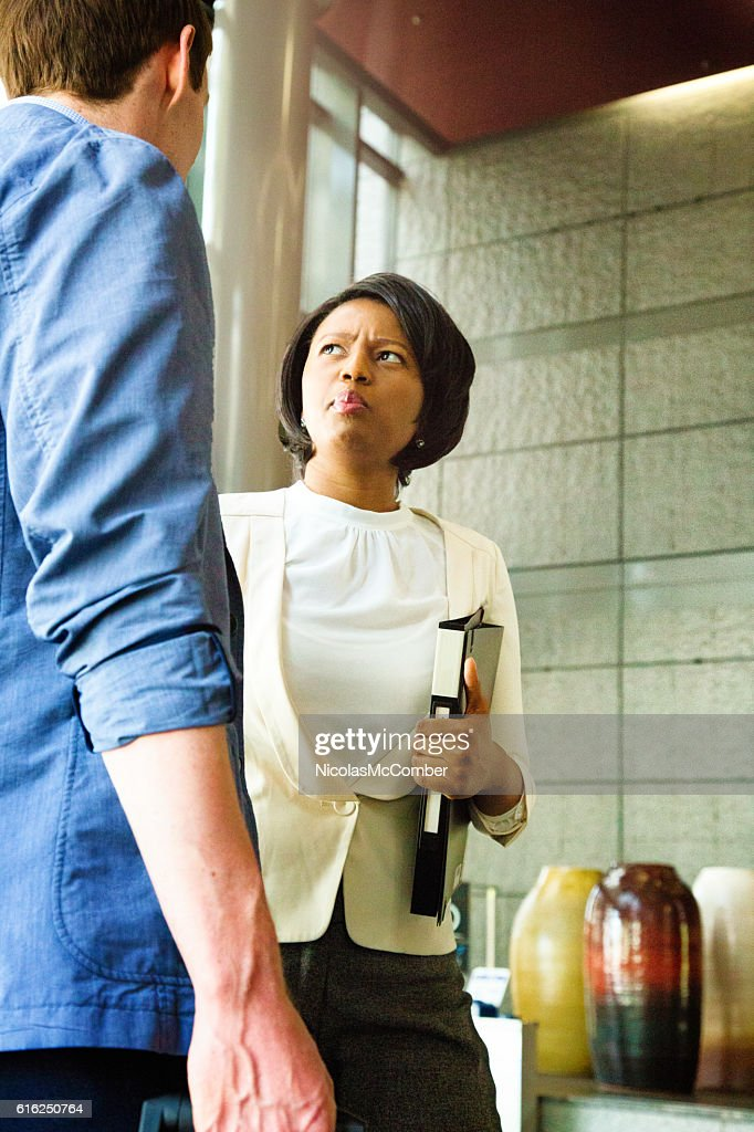 Businesswoman distraught by pre-meeting briefing in lobby : Stock Photo