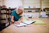 Senior businesswoman is doing paperwork in her stock factory.