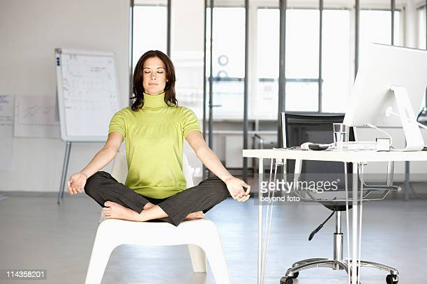 businesswoman doing yoga in office