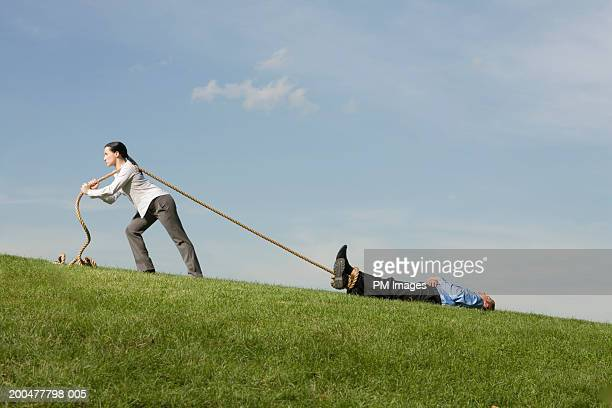 Businesswoman dragging businessman across field with rope, side view