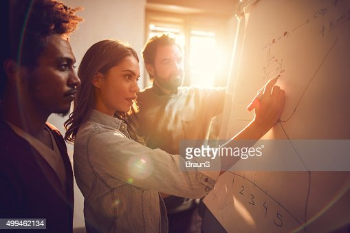 Businesswoman drawing a graph together with her two male colleagues.