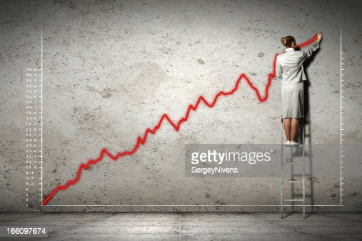 businesswoman drawing diagrams on wall : Stock Photo