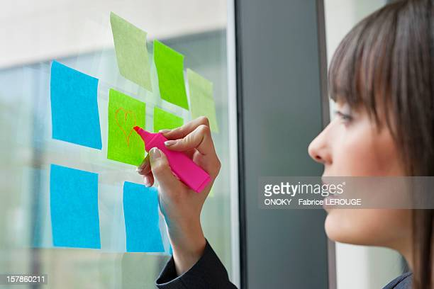Businesswoman drawing heart shape on an adhesive note in an office