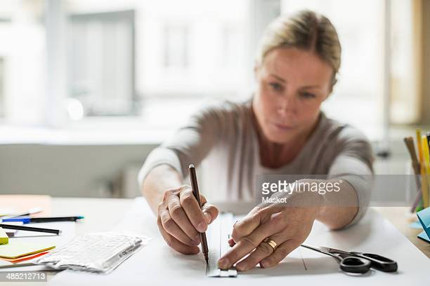 Businesswoman drawing line using ruler on paper