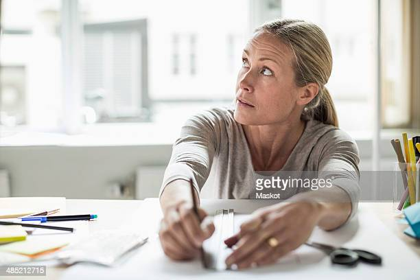 Businesswoman drawing line using ruler on paper while looking away