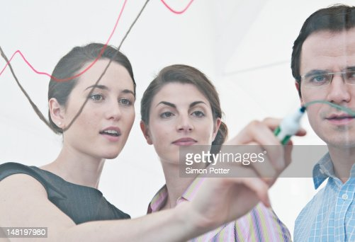 Businesswoman drawing on glass : Stock Photo