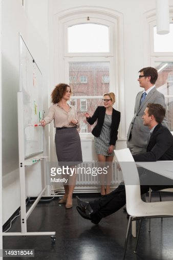 Businesswoman drawing on whiteboard : Stock Photo