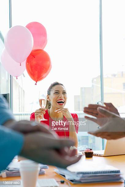 Businesswoman drinking at office party