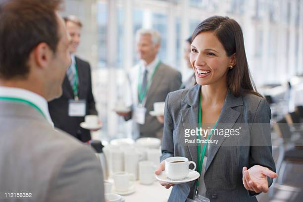 Businesswoman drinking coffee and talking to co-worker