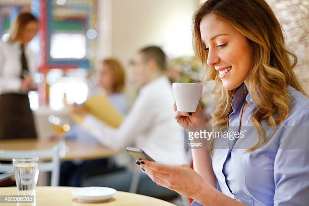 Businesswoman drinking coffee and texting in a restaurant.