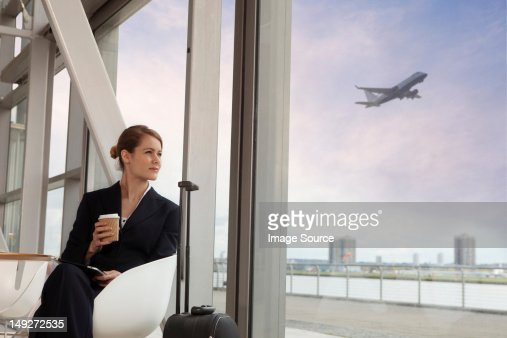 Businesswoman drinking coffee in airport