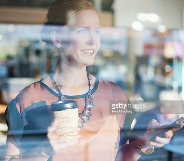 カフェでコーヒーを飲みながらのビジネスウーマン