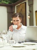 Businesswoman drinking tea in restaurant, looking at laptop