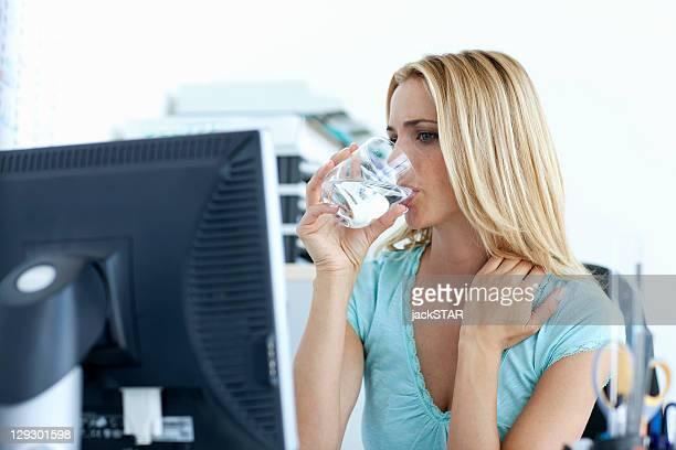 Femme d'affaires au bureau boire de l'eau