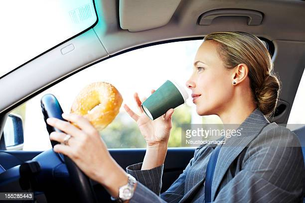 Businesswoman Driving to Work and Having Breakfast.