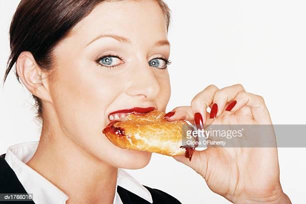 Businesswoman Eating a Strawberry Jam Doughnut