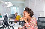 Businesswoman eating burger at desk