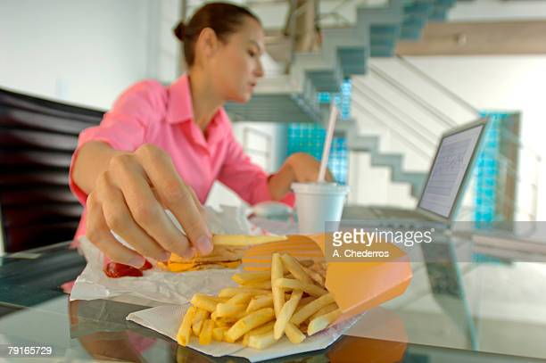 Businesswoman eating French fries, using laptop