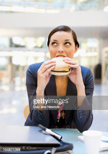 Businesswoman eating hamburger at desk in office : Stock Photo
