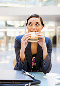 Businesswoman eating hamburger at desk in office