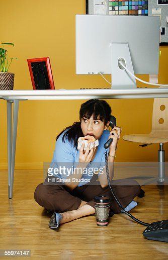 Businesswoman eating lunch under desk