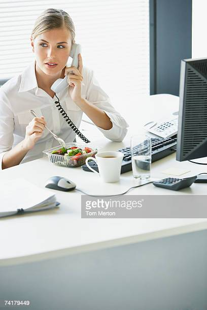 Businesswoman eating salad and talking on telephone at desk