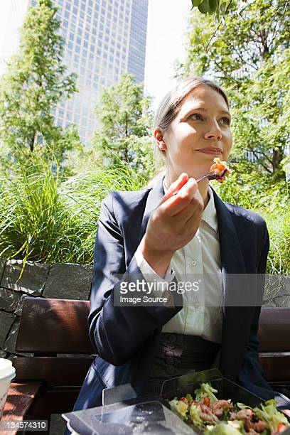 Businesswoman eating salad outdoors