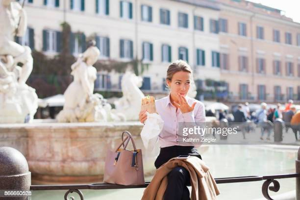 Businesswoman eating sandwich on her lunch break at Piazza Navona, Rome, Italy