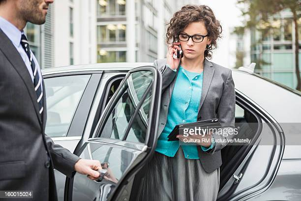 Businesswoman emerging from car