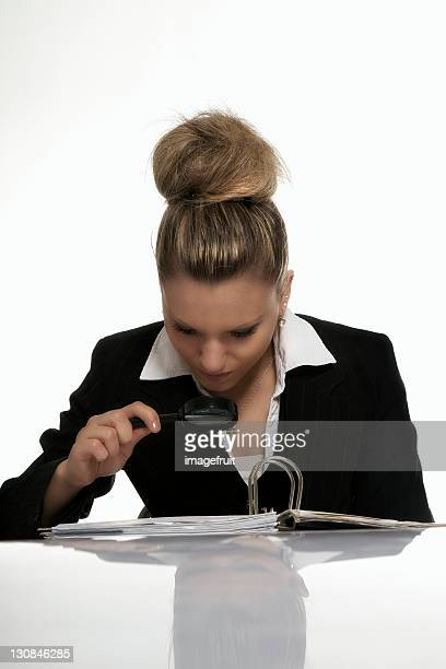 Businesswoman examining business documents with a magnifying glass