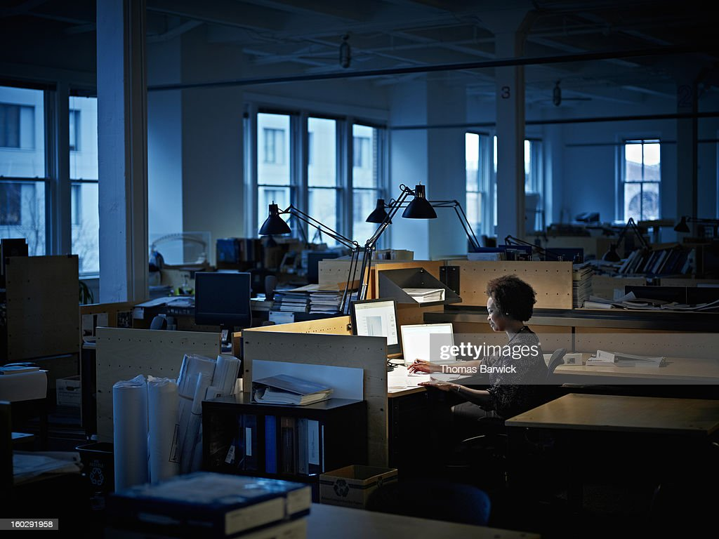 Businesswoman examining documents at desk at night : Stock Photo