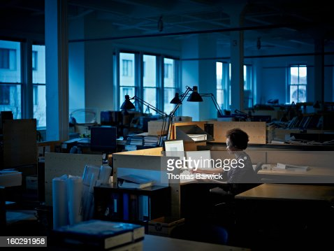 Businesswoman examining documents at desk at night