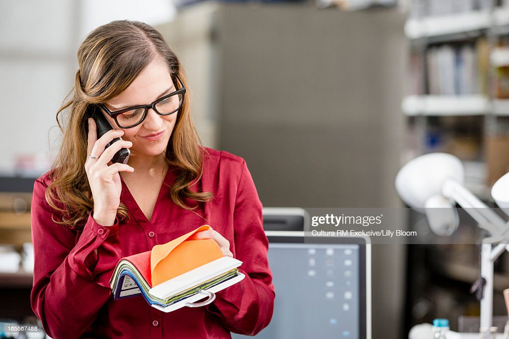 Businesswoman examining fabric swatches : Stock Photo