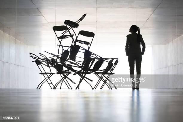 Businesswoman examining office chair installation art