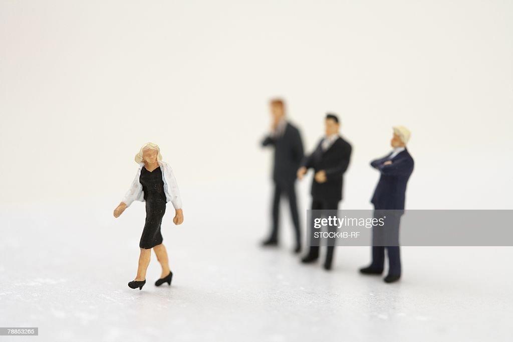 Businesswoman figurine, three businessmen figurines in background