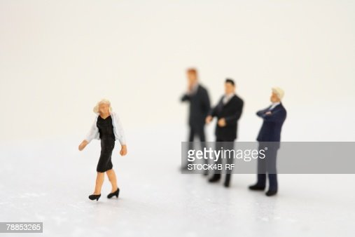 Businesswoman figurine, three businessmen figurines in background