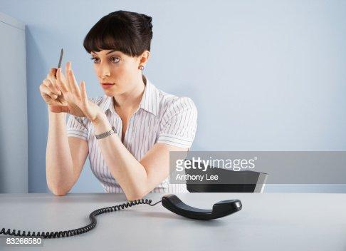 Businesswoman filing fingernails and ignoring telephone call