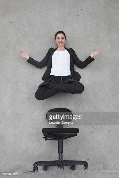 Businesswoman floating above chair, smiling, portrait