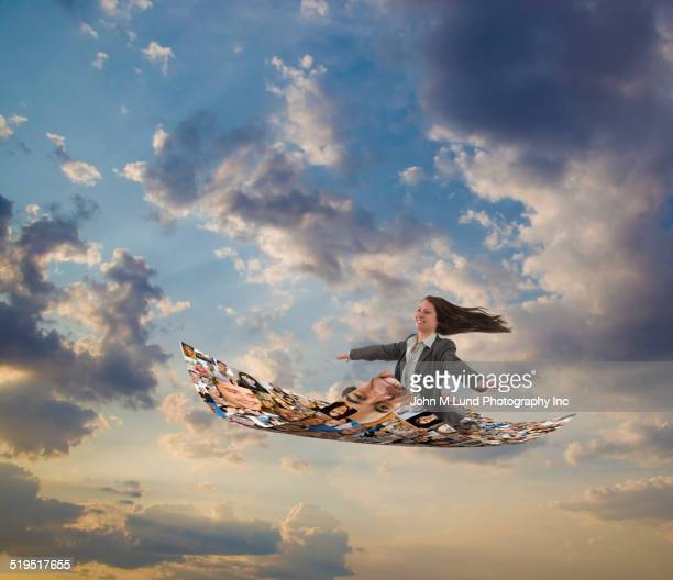 Businesswoman flying on carpet of images of smiling faces