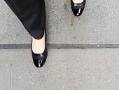 Business woman's feet in dress shoes, standing on one side of line on the ground. Metaphor.
